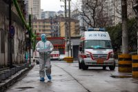 An ambulance crew member carrying medical supplies in Wuhan, China, on Sunday.Credit...CHINATOPIX, via Associated Press