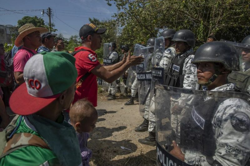 Members of the Mexican National Guard try to block entry to arriving Central American migrants crossing from the Suchiate River in the southern state of Chiapas on Jan. 20. (Alejandro Cegarra/Bloomberg)