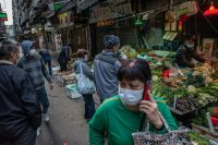 Residents wearing face masks shop at a market in Macao, China. Health officials locked down Wuhan and neighboring cities in an effort to contain the spread of the pneumonia-like disease. (Anthony Kwan/Getty Images)