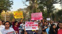 Protestors hold up their signs at the Gowali Tank Maidan in Mumbai.