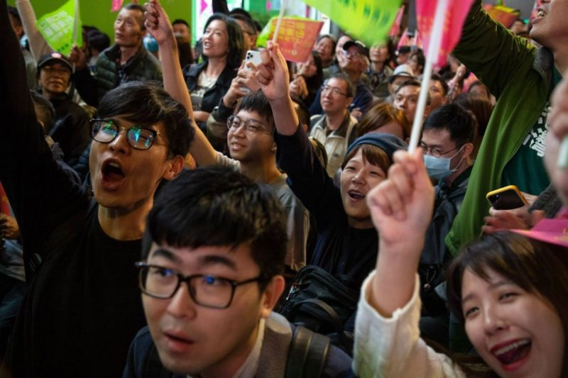 Attendees watch a screen where election results are projected during a Democratic Progressive Party rally with Taiwanese President Tsai Ing-wen in Taipei on Saturday. (Betsy Joles/Bloomberg)