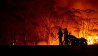 Residents look on as flames burn through bush on 4 January 2020 in Lake Tabourie, NSW. Photo: Getty Images.