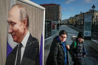 People walk near an image of Russian President Vladimir Putin on Monday in central Moscow. (Yuri Kochetkov/EPA-EFE/Shutterstock)