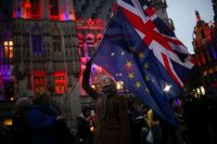 A woman waving the flags of the United Kingdom and the European Union in Brussels on Thursday.Credit...Francisco Seco/Associated Press
