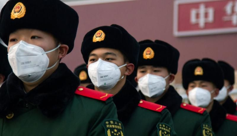 Chinese police officers wearing masks stand in front of the Tiananmen Gate on 26 January. Photo: Getty Images.