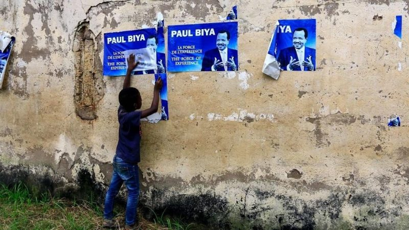A young child holds posters of Cameroonian President Paul Biya on a wall in Yaoundé on November 6, 2018. AFP/STR