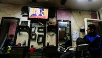 Palestinians watch the televised press conference of Donald Trump and Benjamin Netanyahu on 28 January 2020 at a barber shop in Gaza City. Photo: Getty Images.