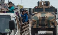 Displaced Syrians and a Turkish military armoured vehicle in Idlib, Syria. Photograph: Burak Kara/Getty Images