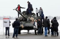 People pose on T-72 battle tank during a Defender of the Fatherland Day celebration Feb. 23 at a former airport in Luhansk, Ukraine. (Dave Mustaine/EPA-EFE/Shutterstock)