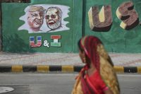 A woman walks by a wall in Ahmadabad, India, with portraits of President Trump and Indian Prime Minister Narendra Modi on Tuesday. ahead of Trump's planned visit to the country. (Ajit Solanki/AP)