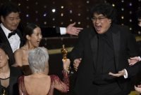 "Bong Joon-ho, right, reacts as presenter Jane Fonda hands him an Oscar for best picture for ""Parasite"" on Sunday. At left are actors Song Kang-ho and Cho Yeo-jeong. (Chris Pizzello/AP)"