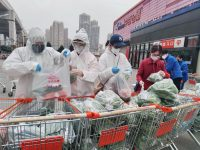 Community workers and volunteers in Wuhan, China, packing groceries purchased through group orders after supermarkets stopped sales to individuals in the midst of the epidemic.Credit...China Daily/Reuters