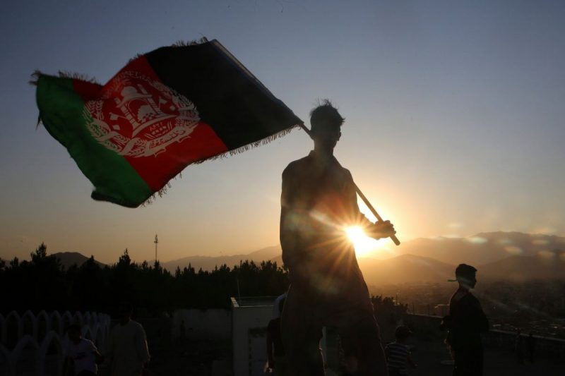 A man waving an Afghan flag during an Independence Day celebration in Kabul in 2019. Credit Rafiq Maqbool/Associated Press