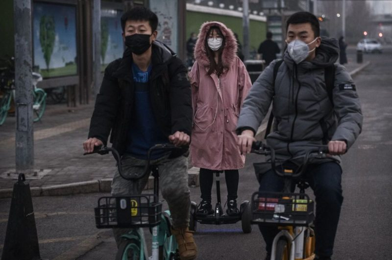 People wear protective masks as they ride in the street in Beijing on Monday. (Kevin Frayer/AFP/Getty Images)