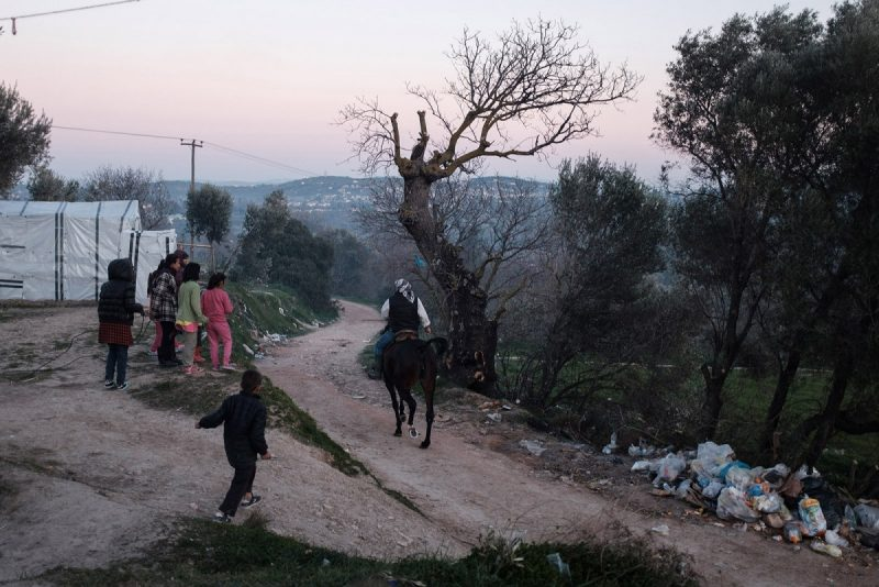 Nick Paleologos/SOOC Refugee children watching a Greek villager riding by their camp, Chios, Greece, February 9, 2020