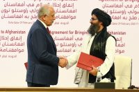 Zalmay Khalilzad, left, an American negotiator, with Mullah Abdul Ghani Baradar, deputy leader of the Taliban, during the signing ceremony of the U.S.-Taliban peace agreement on Saturday.Credit...EPA, via Shutterstock
