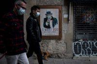 People walk past a poster in Barcelona on Tuesday. (Felipe Dana/AP)