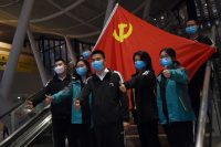 Medical workers from outside Wuhan pose for pictures with a Chinese Communist Party flag at the Wuhan Railway Station before leaving the epicentre of the novel coronavirus outbreak on Tuesday. (Stringer/Reuters)