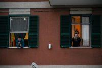 Personas tocan el himno nacional de Italia desde las ventanas de sus casas para animar la cuarentena por coronavirus en Roma, el 13 de marzo de 2020. (ANDREAS SOLARO/AFP vía Getty Images)