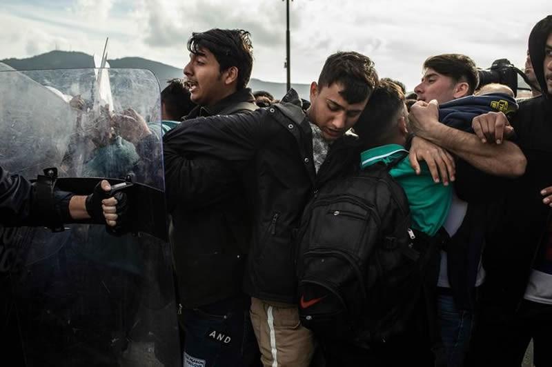 Des migrants font face à la police grecque, le 3 mars, sur l'île de Lesbos. Photo Angelos Tzortzinis. AFP