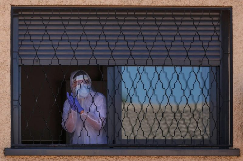 A member of the Military Emergencies Unit appears at a window during a disinfection in the Getafe suburb of Madrid on 25 March. Photograph: Baldesca Samper/AFP via Getty Images