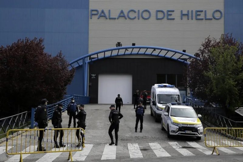Police officers stand in front of an ice rink turned into a temporary morgue in Madrid on 24 March. Photograph: Manu Fernández/AP