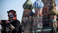 Young woman wearing a face mask in front of St. Basil's Cathedral, Moscow. Photo by ALEXANDER NEMENOV/AFP via Getty Images.
