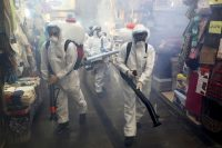 Firefighters disinfect a shopping center in Tehran on Friday. (Ebrahim Noroozi/AP)