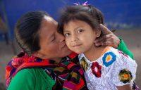 Una madre besa a su hija en Guatemala. Educo