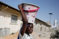A girl carries a bucket of clean water in Pikine near Dakar, Senegal, on March 9. (Zohra Bensemra/Reuters)