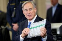 Tom Pennington/Getty Images Texas Governor Greg Abbott displaying Covid-19 test collection vials during a press conference, Arlington, Texas, March 18, 2020