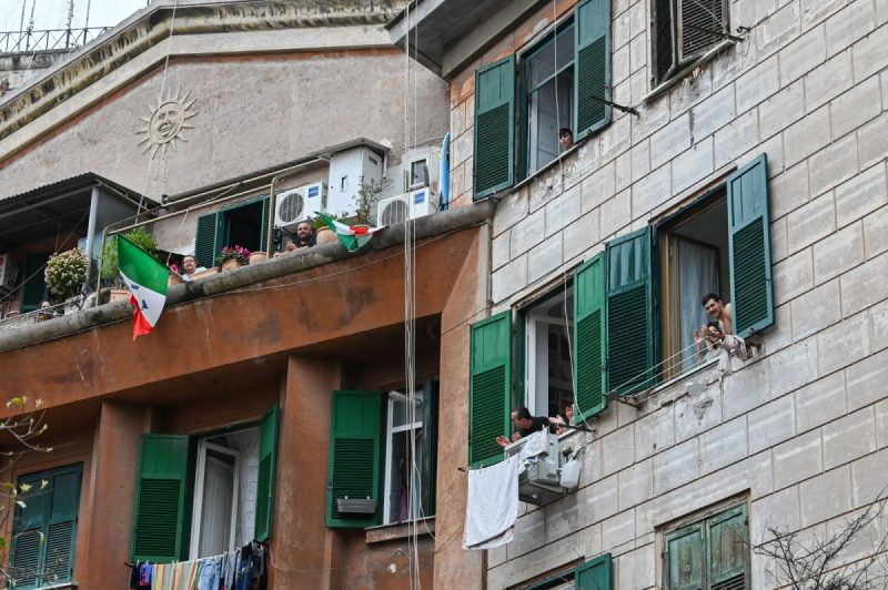 """Andreas Solaro/AFP via Getty Images People cheering from their balconies during the daily flash mob """"An applause for Italy,"""" in the Garbatella district in Rome, Italy, March 14, 2020"""
