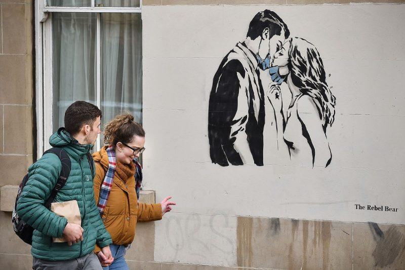 Jeff J Mitchell/Getty Images A couple passing a mural of a mask-wearing couple kissing, Glasgow, Scotland, March 21, 2020