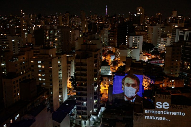 Miguel Schincariol/Getty Images An image of President Jair Bolsonaro wearing a face mask projected onto a building's wall during a Panelaço balcony protest, São Paulo, Brazil, March 19, 2020