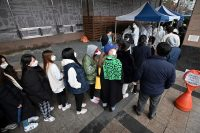 Workers from a building where 46 people were confirmed to have the coronavirus wait in line for testing at a temporary facility in Seoul on Monday. (Jung Yeon-je/AFP via Getty Images)