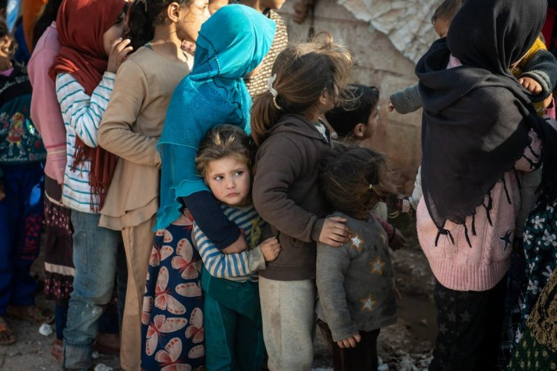 Displaced Syrian children wait in line to receive humanitarian aid supplied by Humanitarian Relief Foundation's on Feb. 20 in Idlib, Syria. (Burak Kara/AFP/Getty Images)