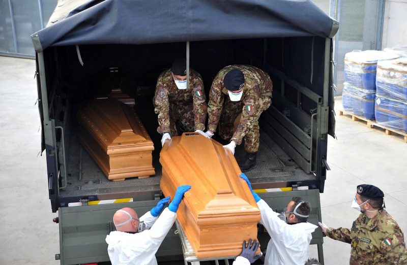 Photo by SERGIO PESCI/EPA-EFE/Shutterstock. Italian army trucks are loaded with coffins to be transported to a crematorium. (Sergio Pesci/EPA-EFE/REX/Shutterstock)