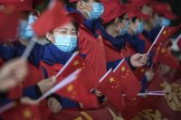 Volunteers waving the Chinese flag send off the China national emergency medical team at the Tianhe airport in Wuhan, China, on Tuesday. (Stringer/AFP/Getty Images)
