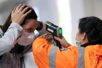 Checking the temperature of a passenger arriving at the international airport in Hong Kong. The city, like Singapore and Taiwan, has made headway in containing Covid-19.