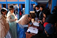 A woman signs on a voters record after voting at a polling station during general elections in La Paz outskirts, Bolivia, Sunday, Oct. 20, 2019. (Jorge Saenz)