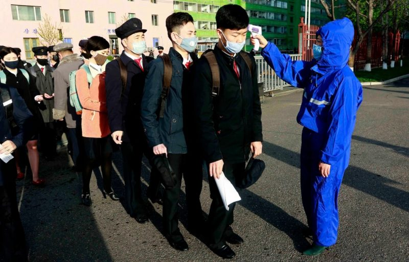 Students wearing masks have their temperatures checked Wednesday as a precaution against coronavirus as Kim Chaek University of Technology in Pyongyang reopened. (Jon Chol Jin/AP)