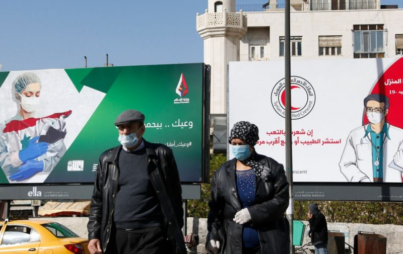 Syrians wearing face masks walk past billboards with messages about the coronavirus in Damascus on April 1. (Louai Beshara/AFP via Getty Images)