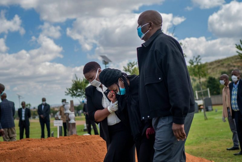 Relatives attend the funeral of Benedict Somi Vilakasi at the Nasrec Memorial Park near Johannesburg on Thursday. Vilakasi, a Soweto coffee shop manager, died of covid-19 on Sunday. (Jerome Delay/AP)
