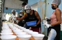 People prepare food to give to homeless people in Rio de Janeiro on April 11. (Lucas Landau/Reuters)