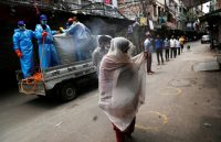 Municipal workers spray disinfectant on people lining up at a mobile testing station for the coronavirus in New Delhi. (Adnan Abidi/Reuters)