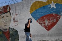 A man wearing a protective face mask walks past a mural of the late Venezuelan President Hugo Chávez in Caracas on April 11. (Matias Delacroix/AP)