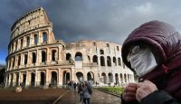 A man with a protective mask by the Coliseum in Rome during the height of Italy's COVID-19 epidemic. Photo by ALBERTO PIZZOLI/AFP via Getty Images.