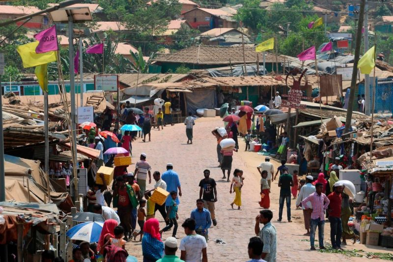 Rohingya refugees walk in a market area in Kutupalong refugee camp in Bangladesh on March 24. (Suzauddin Rubel/AFP via Getty Images)