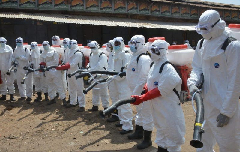 Workers dressed in full body gear prepare to disinfect shops and streets in Conakry, Guinea, on April 12 during a cleaning and disinfecting campaign as a preventive measure against the spread of the coronavirus. (Cellou Binani/Afp Via Getty Images)