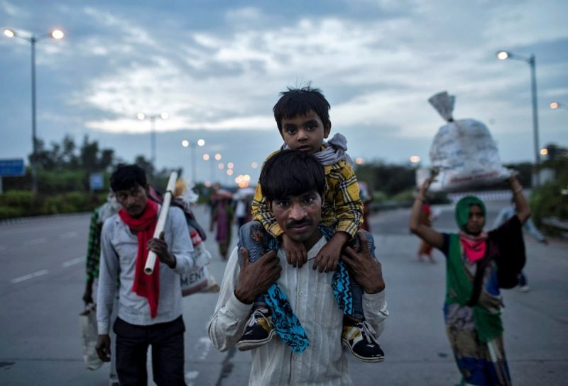A migrant worker carried his 5-year-old son in New Delhi as they returned to their village during India's nationwide lockdown to limit the spreading of the coronavirus. (Danish Siddiqui/Reuters)